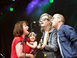 Amy Millan holding daughter Delphine while singing with Brendan Canning and Torquil Campbell.